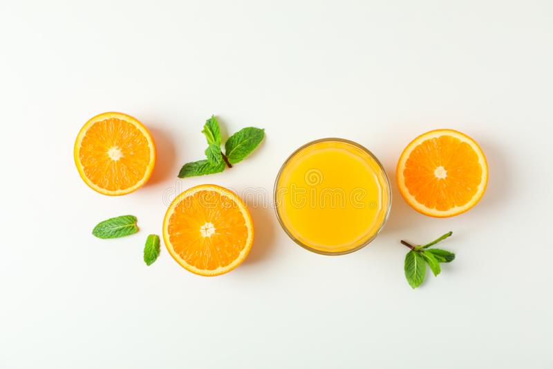 Composición puesta plana con el zumo, las naranjas y la menta de naranja en el fondo blanco, espacio para el texto Bebida de la f imagen de archivo