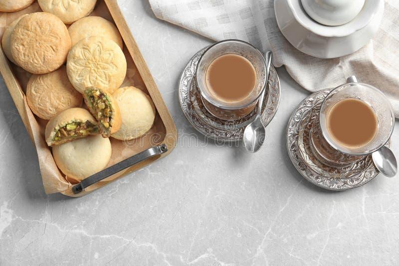 Composición puesta plana con la bandeja de galletas para los días de fiesta islámicos y las tazas Eid Mubarak fotos de archivo libres de regalías