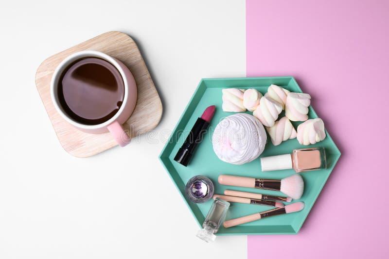 Composición puesta plana con la bebida, los dulces y los cosméticos fotos de archivo