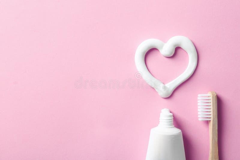 Composición puesta plana con la forma del corazón hecha de la crema dental y del espacio para el texto en fondo del color imagen de archivo