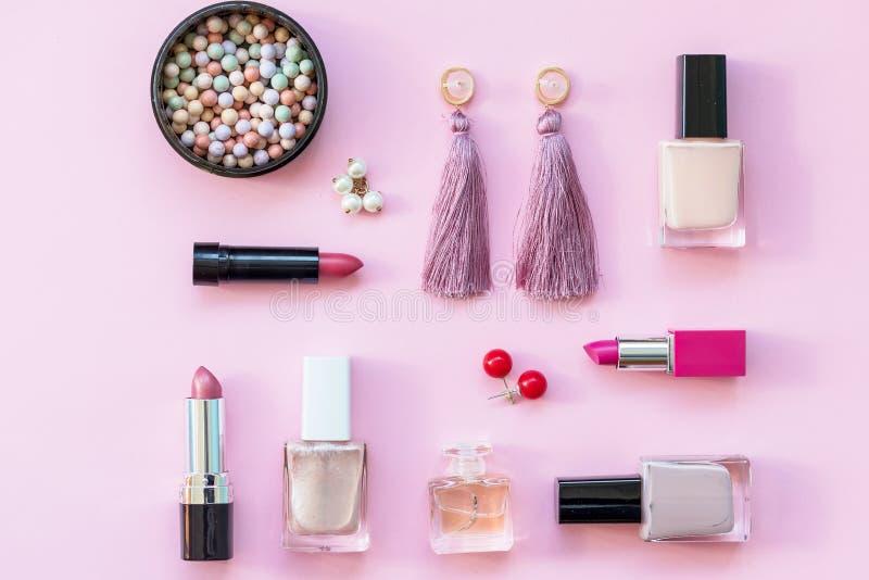 Composición puesta plana con la fundación de la piel, el polvo y los accesorios de la belleza en fondo rosado Sistema cosmético d foto de archivo