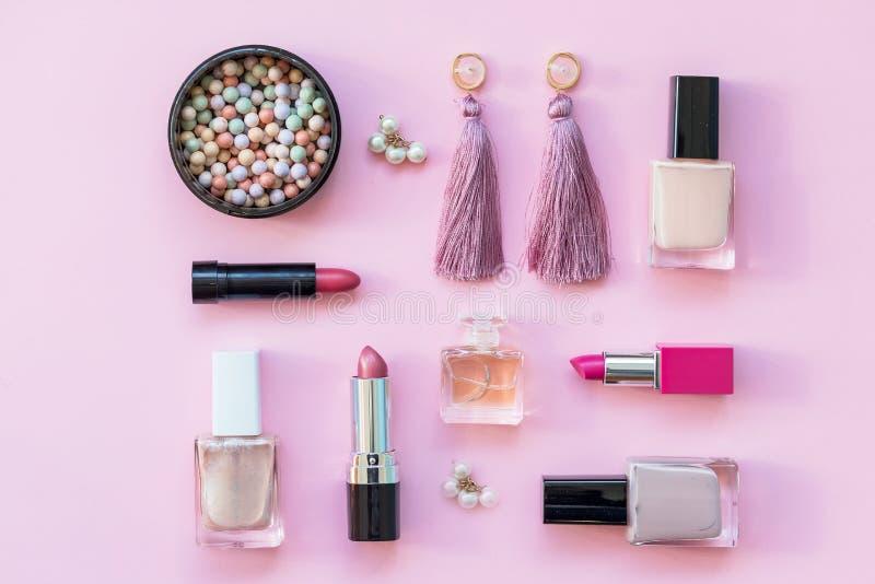 Composición puesta plana con la fundación de la piel, el polvo y los accesorios de la belleza en fondo rosado Sistema cosmético d imagenes de archivo