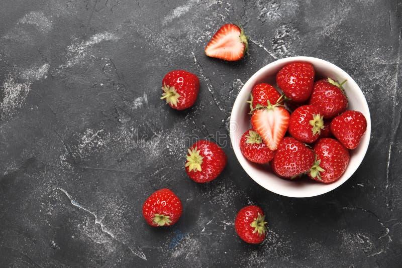 Composición puesta plana con las fresas rojas maduras en fondo negro imagenes de archivo