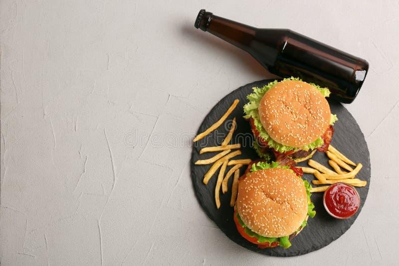 Composición puesta plana con las hamburguesas, las patatas fritas y la botella en fondo gris imagen de archivo