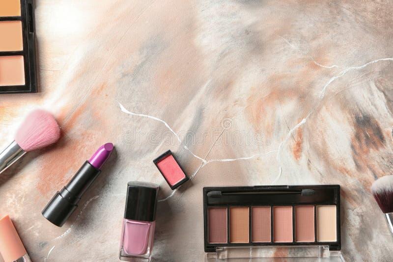 Composición puesta plana con los cosméticos decorativos en el fondo de mármol foto de archivo