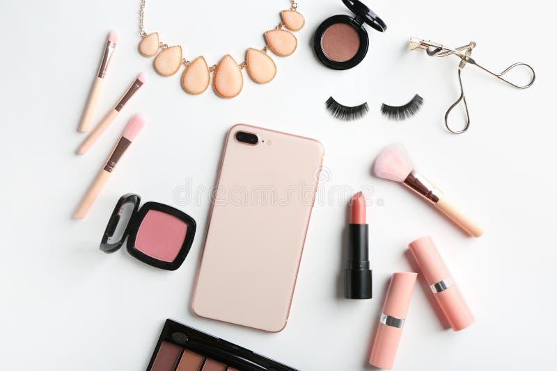 Composición puesta plana con los cosméticos decorativos y el teléfono móvil en el fondo blanco imágenes de archivo libres de regalías