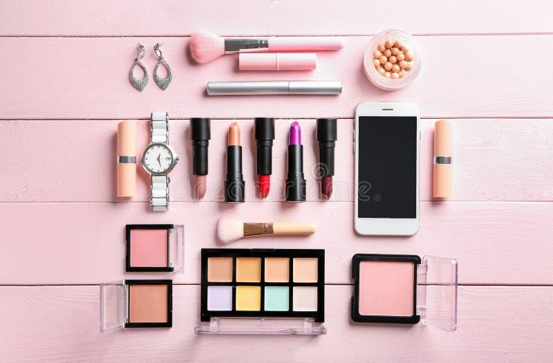 Composición puesta plana con los cosméticos decorativos y el teléfono móvil en fondo de madera del color imágenes de archivo libres de regalías