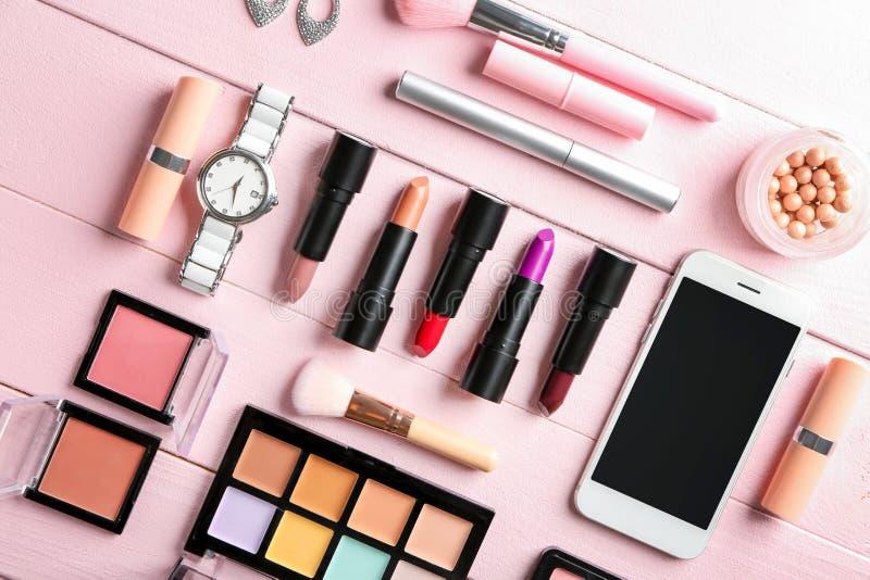 Composición puesta plana con los cosméticos decorativos y el teléfono móvil en fondo de madera del color imagen de archivo