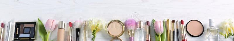 Composición puesta plana con los diversos cosméticos y flores decorativos en la tabla de madera foto de archivo