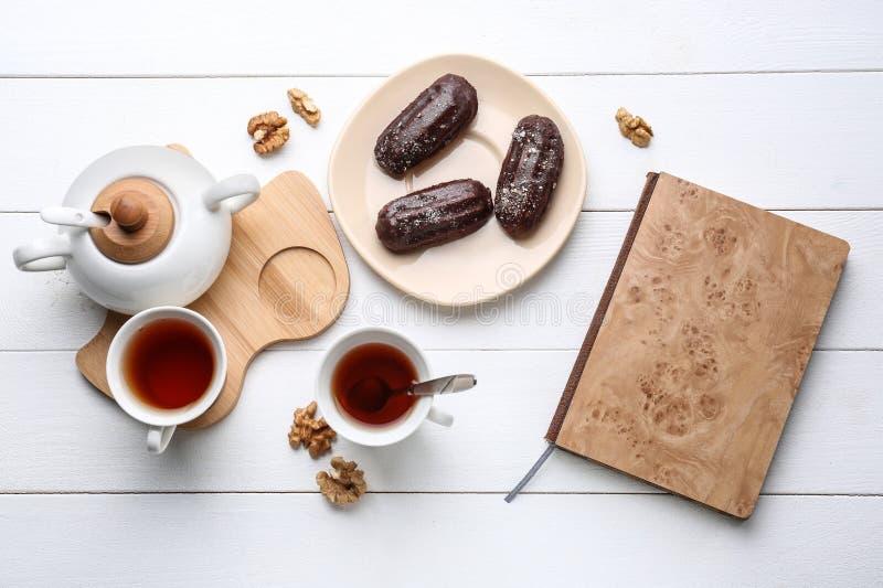 Composición puesta plana con los eclairs y el té deliciosos en la tabla fotos de archivo