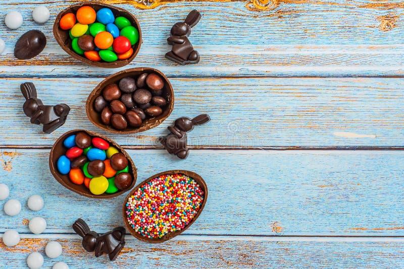 Composición puesta plana con los huevos, el conejo y los dulces de Pascua del chocolate en fondo de madera azul Visión superior C imagen de archivo libre de regalías
