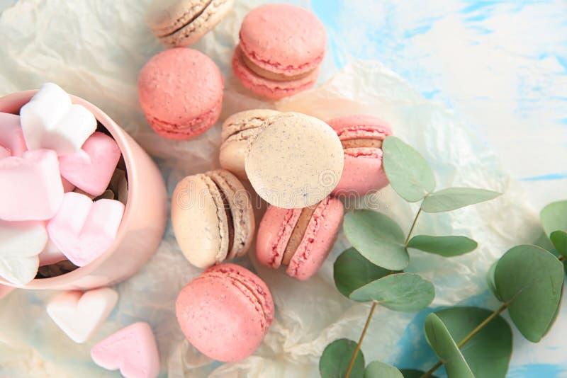 Composición puesta plana con los macarons y las melcochas sabrosos en la tabla imagen de archivo libre de regalías