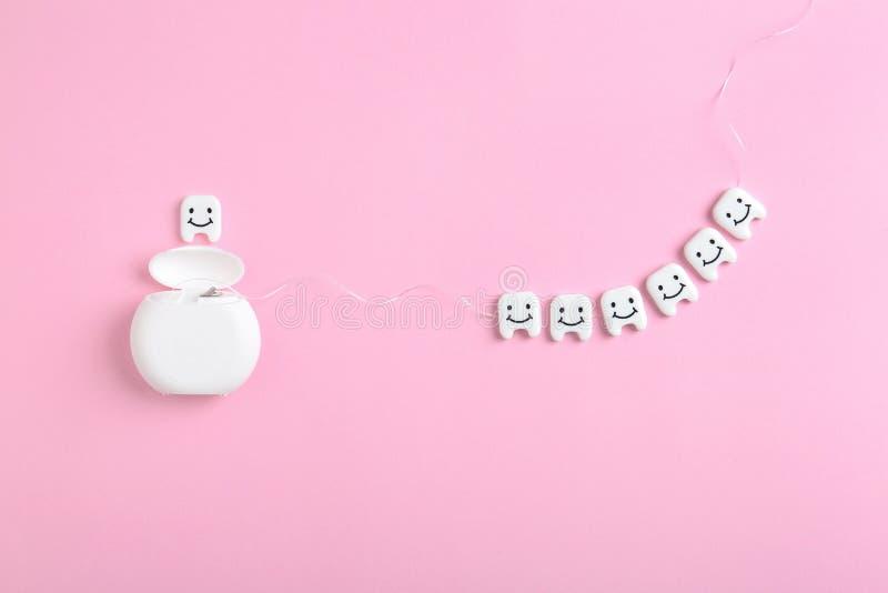 Composición puesta plana con los pequeños dientes plásticos y la seda dental imagen de archivo