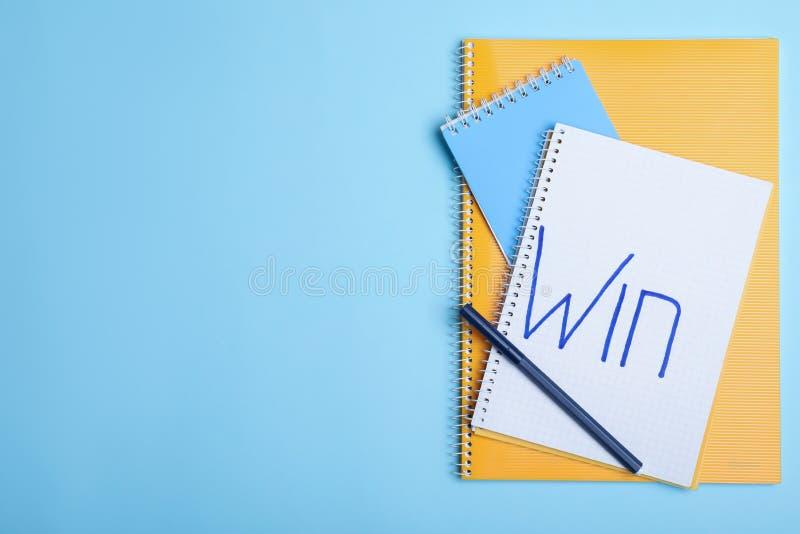 Composición puesta plana de cuadernos con triunfo y el espacio de la palabra para el texto en fondo del color fotografía de archivo