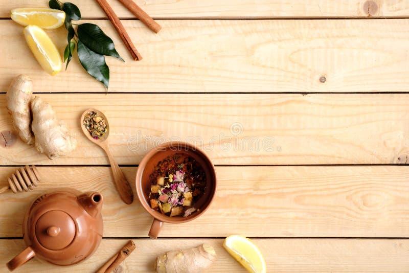 Composición puesta plana de la infusión de hierbas, accesorios del té, miel, cuchara del té secado, hojas de la planta, raíz del  fotografía de archivo