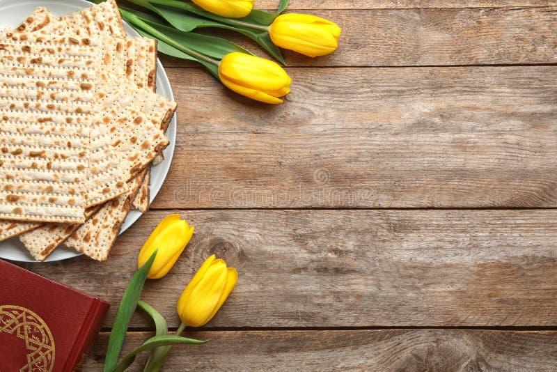 Composición puesta plana del matzo, de Torah y de flores en el fondo de madera, espacio para el texto fotografía de archivo