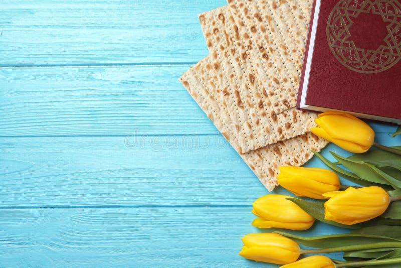 Composición puesta plana del matzo, de Torah y de flores en el fondo de madera, espacio para el texto imagenes de archivo