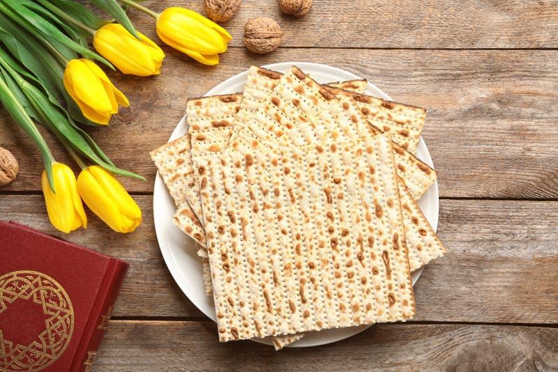 Composición puesta plana del matzo, de Torah y de flores en fondo de madera fotografía de archivo libre de regalías