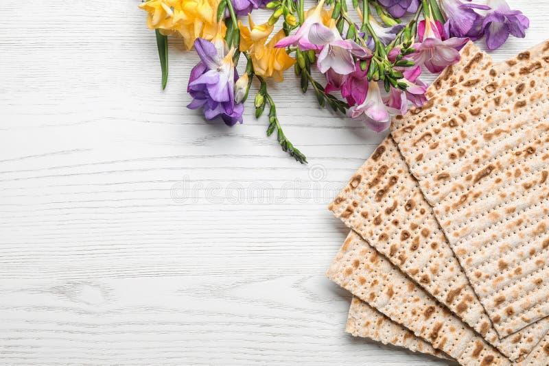 Composición puesta plana del matzo y de flores en fondo de madera Pascua judía Pesach Seder foto de archivo