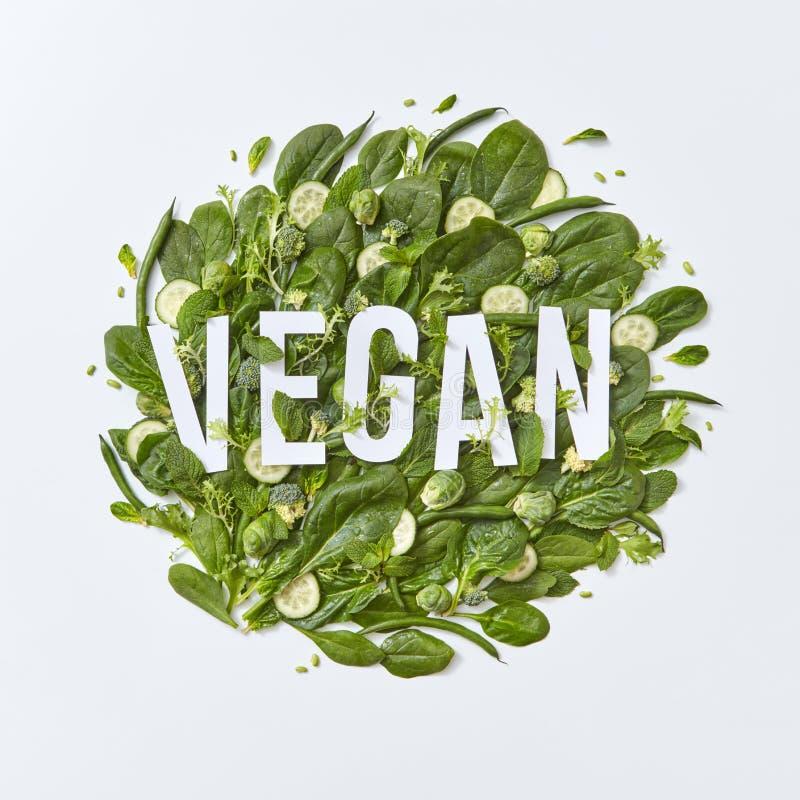 Composición redonda de diversas verduras verdes con las letras del papel del vegano en un fondo gris con el espacio de la copia S foto de archivo