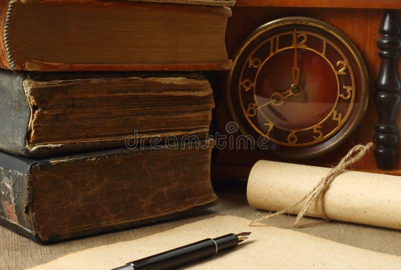 Composición retra con los libros, el reloj, el papel y la pluma fotografía de archivo