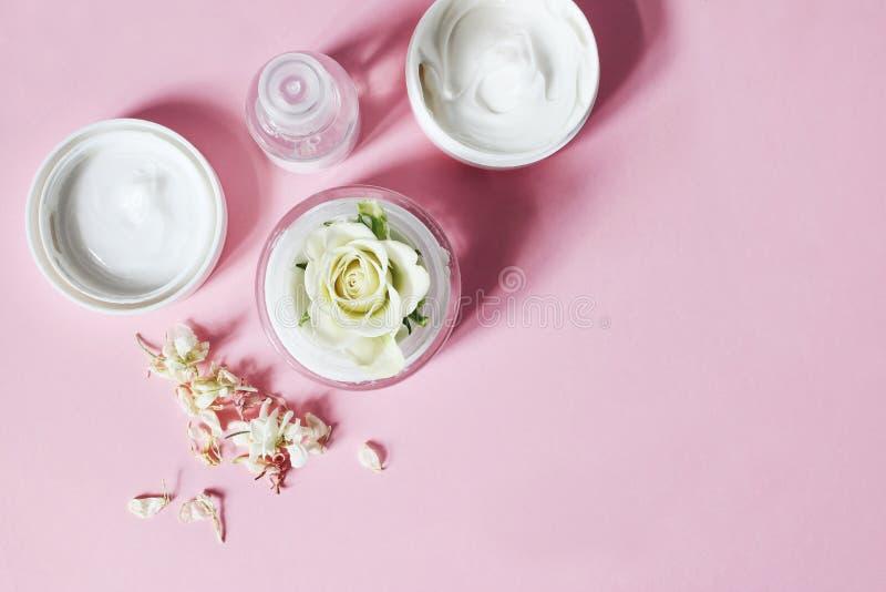 Composición soleada de la belleza Primer de la crema de piel, de la botella del tonicum, de flores secas y de la rosa con las som imagen de archivo libre de regalías