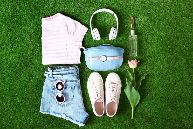 Composici?n con la ropa y los accesorios de las mujeres elegantes para la primavera en hierba verde imagen de archivo libre de regalías