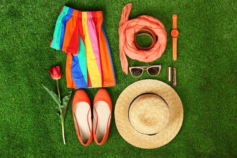 Composici?n con la ropa y los accesorios de las mujeres elegantes para la primavera en hierba verde imágenes de archivo libres de regalías