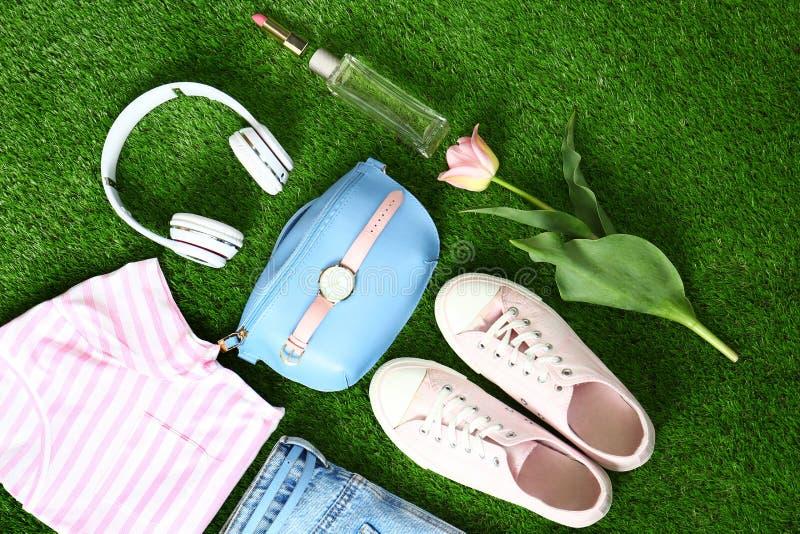 Composici?n con la ropa y los accesorios de las mujeres elegantes para la primavera en hierba verde foto de archivo libre de regalías