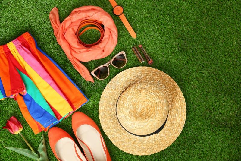 Composici?n con la ropa y los accesorios de las mujeres elegantes para la primavera en hierba verde imagenes de archivo