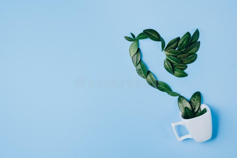 Composici?n creativa Taza de caf? con el p?jaro hecho de hojas verdes naturales en fondo azul Endecha plana, visi?n superior, esp ilustración del vector