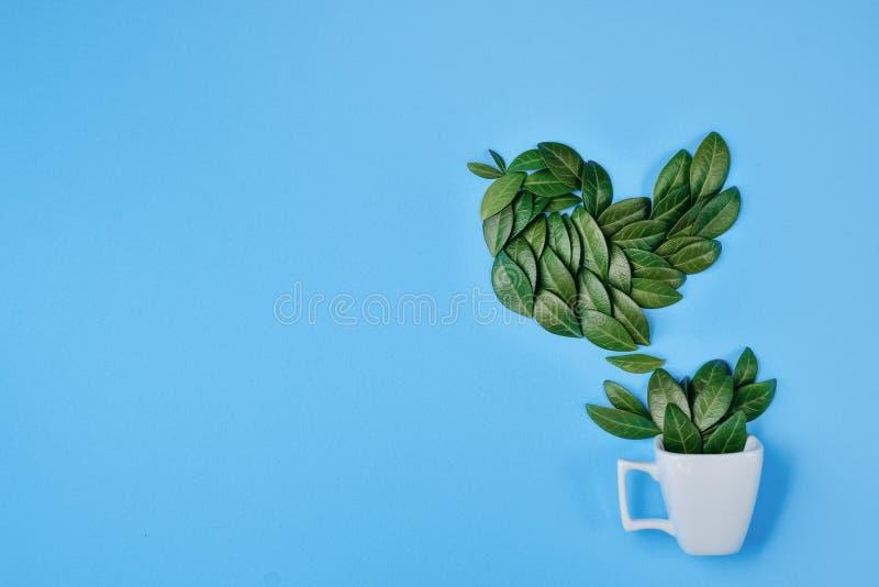 Composici?n creativa Taza de caf? con el p?jaro hecho de hojas verdes naturales en fondo azul Endecha plana, visi?n superior, esp stock de ilustración