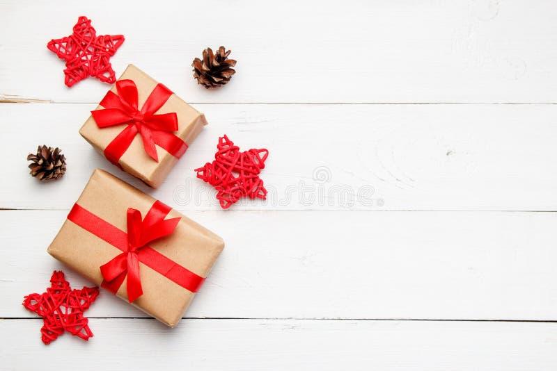 Composici?n de la Navidad Regalos de la Navidad con las estrellas decorativas rojas de la rota y conos en fondo blanco de madera  foto de archivo libre de regalías