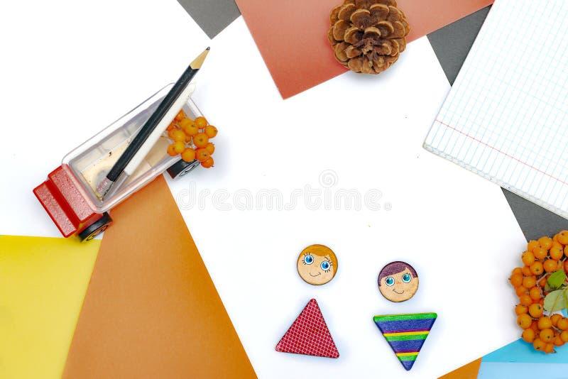 Composici?n del oto?o Figura del juguete, muchacho y muchacha, fuentes de escuela en las hojas del fondo del papel coloreado Copi fotografía de archivo