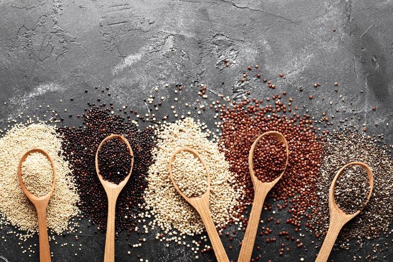 Composici?n puesta plana con diversos tipos de quinoa en fondo negro imagen de archivo