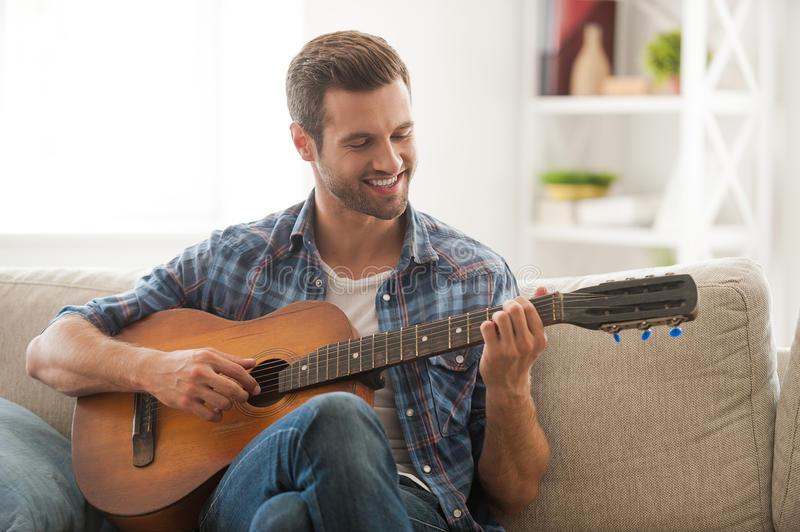 Composing his new song. Happy young man playing the guitar while sitting on sofa at home stock photography