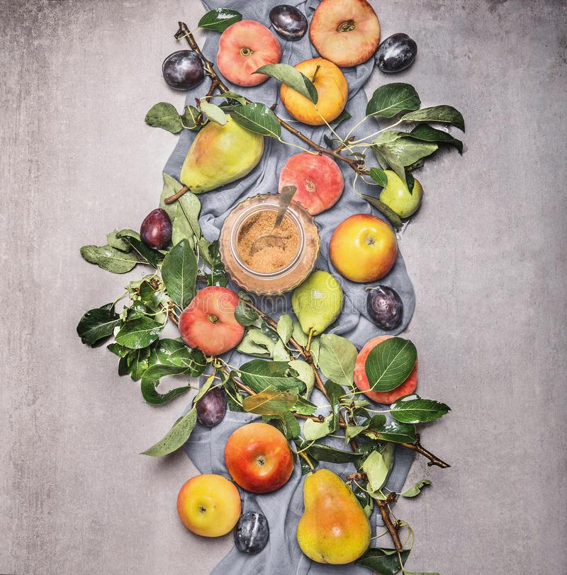Composing of seasonal organic fruits from garden: apples, pears, peaches, plums with leaves and brown raw sugar. top view. Flat. Lay. Healthy clean food stock photo