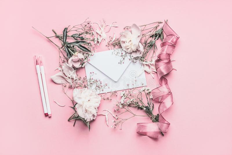 Composing with white peonies, envelope, ribbon and markers on pastel pink background, top view. Copy space for your design royalty free stock image