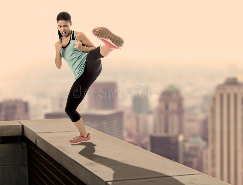 Composite of attractive furious sport woman in fight and martial arts kick workout on urban rooftop edge with a skyline city. View in danger risk and healthy royalty free stock photography