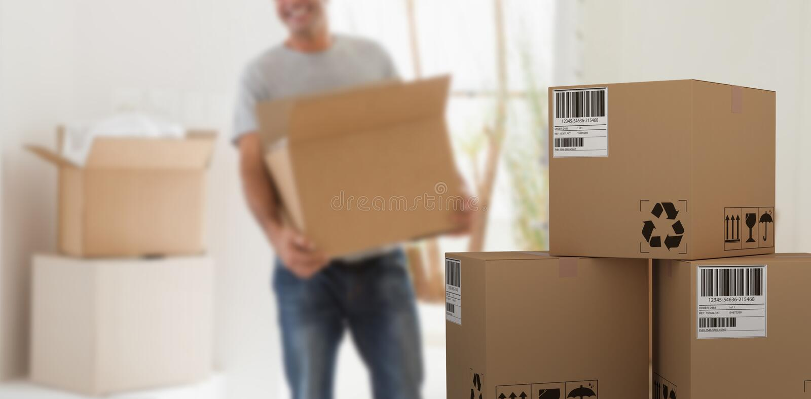 Composite 3d image of graphic image of cardboard courier boxes. Graphic 3D image of cardboard courier boxes against smiling man carrying boxes in new house stock photography