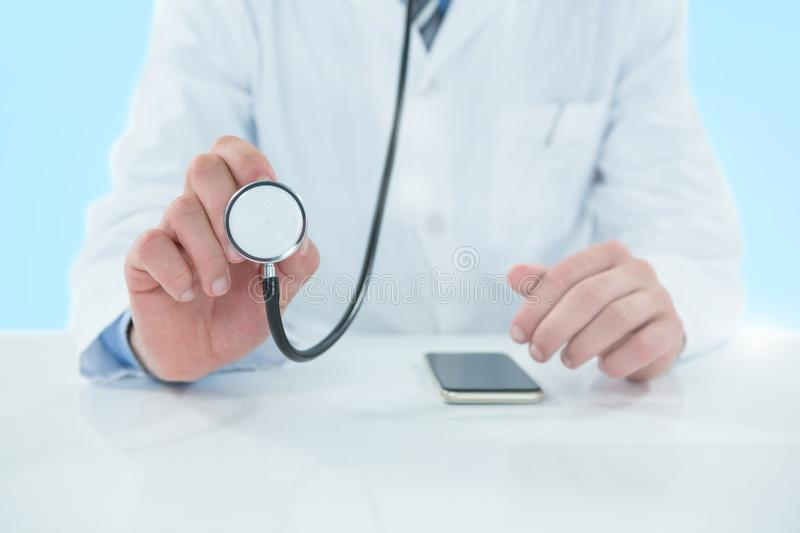 Composite 3d image of midsection of doctor holding stethoscope royalty free stock photo