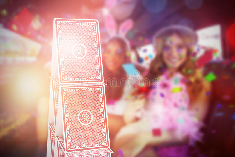 Composite 3d image of portrait of female friends drinking cocktails. Against 3d image of card tower royalty free stock photo