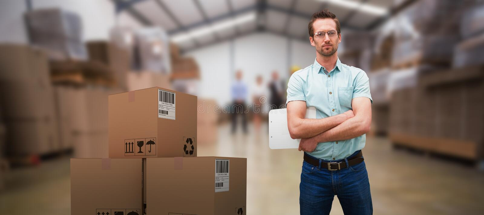 Composite 3d image of serious warehouse manager standing with arms crossed royalty free stock photo
