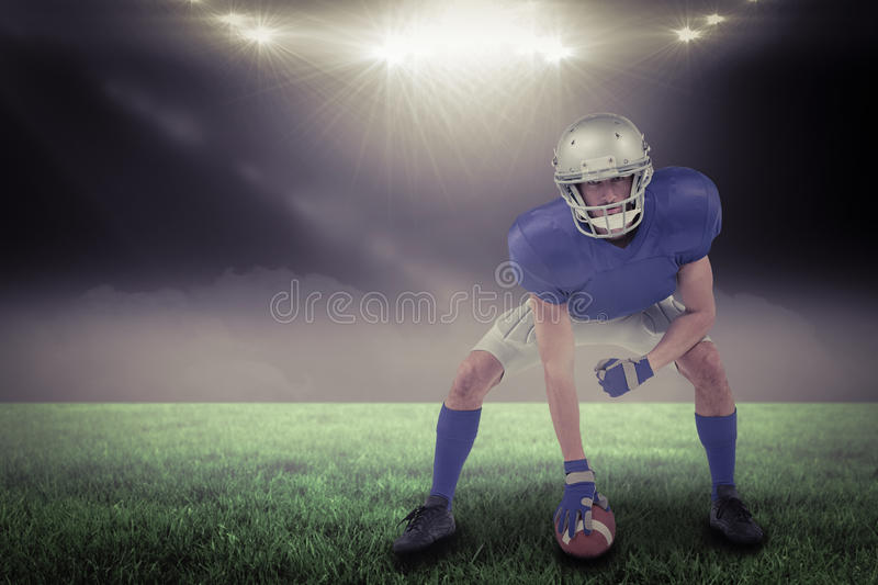 Composite image of american football player in attack stance with 3d. American football player in attack stance against spotlight with copy space 3d stock photography