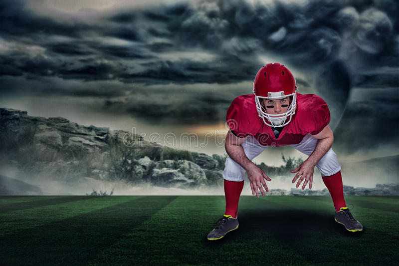 Composite image of american football player in attack stance with 3d. American football player in attack stance against stormy sky with tornado over landscape royalty free stock image