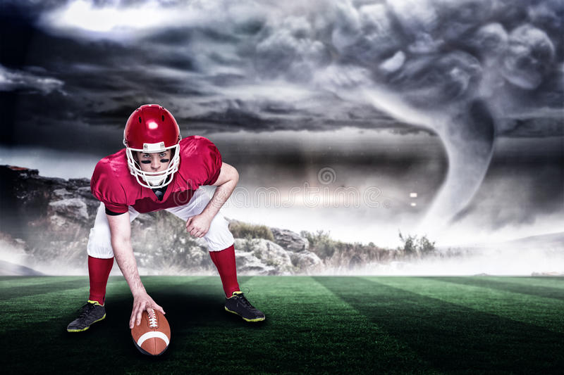 Composite image of american football player in attack stance 3d. American football player in attack stance against stormy sky with tornado over landscape with royalty free stock image
