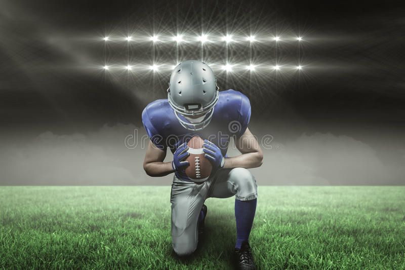 Composite image of american football player kneeling with 3d. American football player kneeling against spotlights with copy space 3d stock images