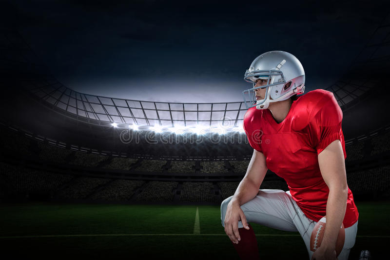 Composite image of american football player looking away while kneeling stock images