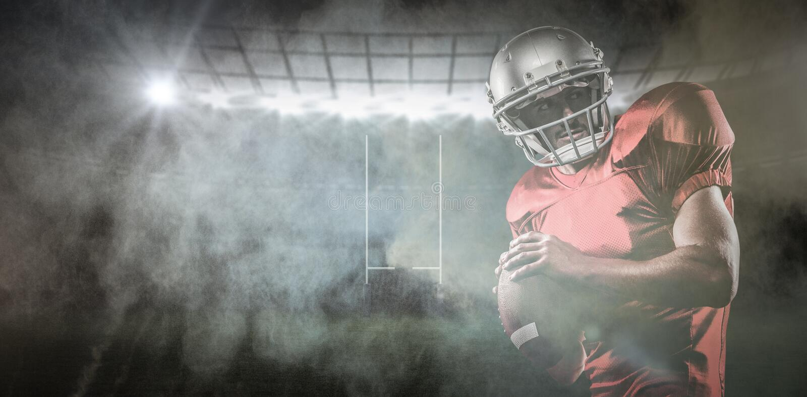 Composite image of american football player in red jersey looking away while holding ball stock photography