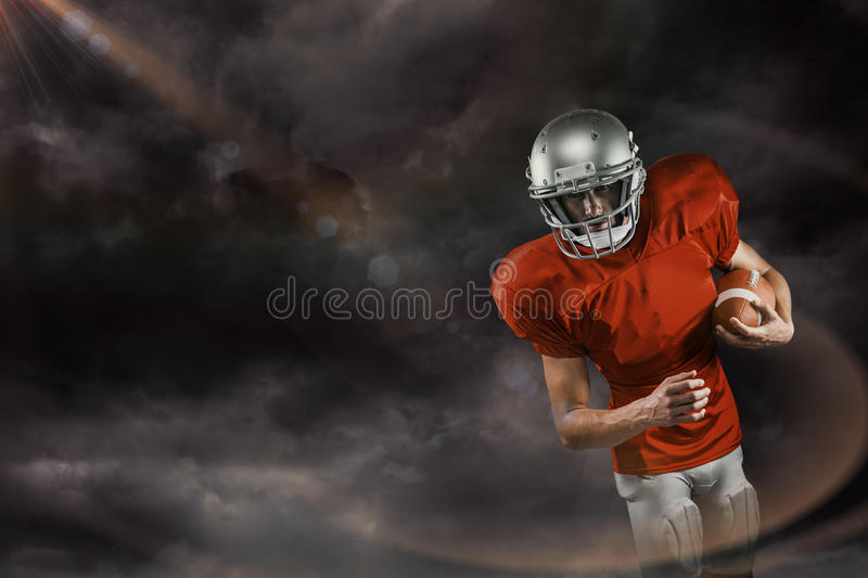 Composite image of american football player in red jersey looking down while holding ball stock photography